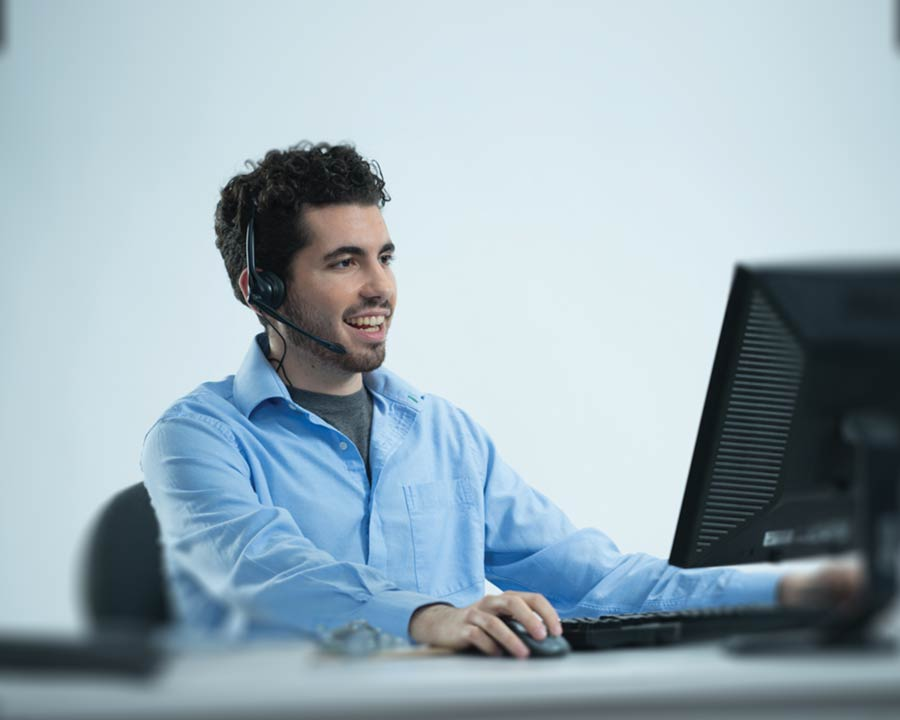 Picture of a customer service representative talking on the phone at a computer
